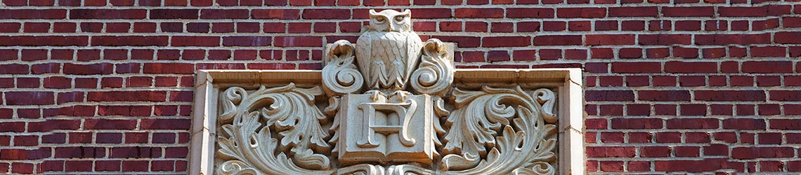 Photo of a stonework owl and book emblem on the outside Eppes Hall l